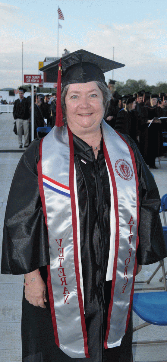 Middle-aged college graduate and Air Force veteran standing, smiling wearing her cap and gown, and veteran's sash