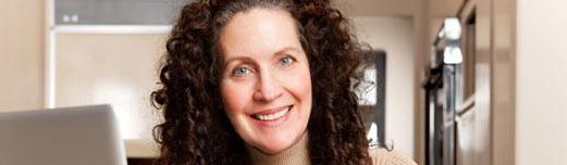Middle aged white woman with big curly, brown sitting at her laptop smiling.